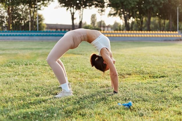 Portret van slanke jonge volwassen vrouw die achterover buigt op het stadionveld, buiten traint, alleen traint, gezondheidszorg, gezonde levensstijl, sportactiviteit in de zomer.