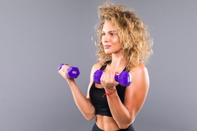 Portret van slanke sportieve vrouw die oefeningen met kleine domoren doet die over grijze muur worden geïsoleerd