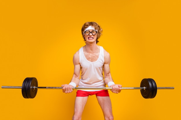 Portret van slanke wanhopige man die zware barbell opheft die duurzaam uitwerkt