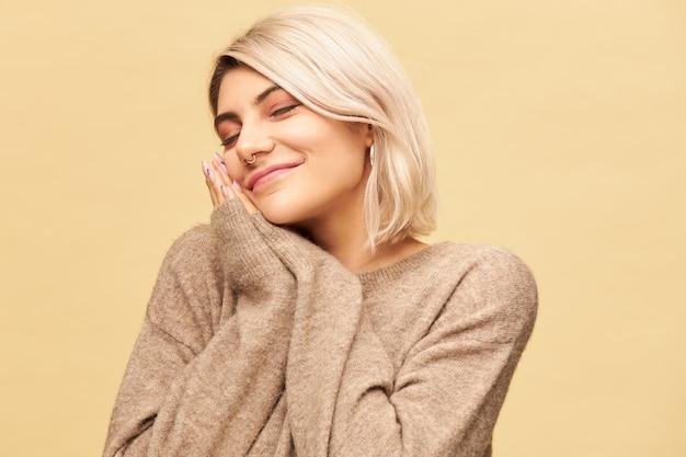 Portret van slaperig vermoeide jonge blonde vrouw met neusring die het hoofd op handen tegen elkaar drukt en de ogen gesloten houdt, een dutje doet of slaapt, gelukkig lachend. slaap, beddengoed en vermoeidheid concept