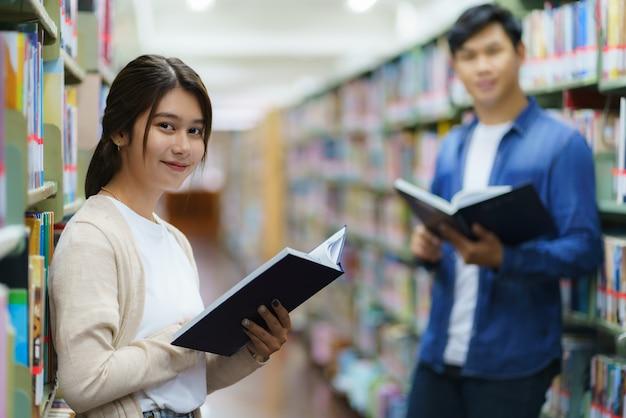 Portret van slimme aziatische man en vrouw universitaire student leesboek