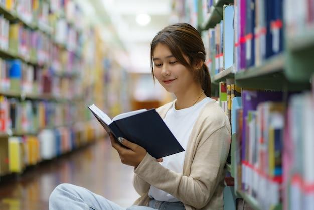 Portret van slimme aziatische vrouw universitaire student leesboek en kijken naar camera tussen boekenkasten in campusbibliotheek met copyspace.