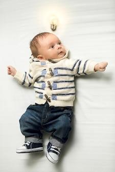 Portret van slimme babyjongen met gloeiende gloeilamp boven je hoofd