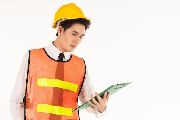 Portret van slimme jonge aziatische ingenieur zakenman dragen wit overhemd, gele veiligheidshelm, veiligheidsvest en helm houden en op zoek naar groen papier klembord op witte achtergrond en kopieer ruimte.