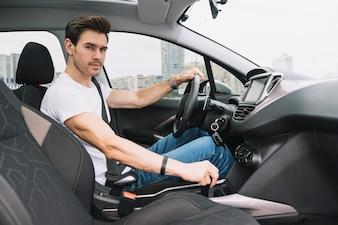 Portret van slimme jonge man zit in de auto rijden