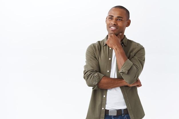 Portret van slimme knappe afro-amerikaanse man, kin aanraken en tevreden glimlachen als uitstekende keuze gevonden Gratis Foto