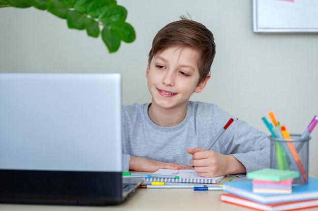 Portret van slimme schooljongen die in notitieboekje schrijft en laptop gebruikt terwijl hij thuis aan het bureau zit schoolwerk.