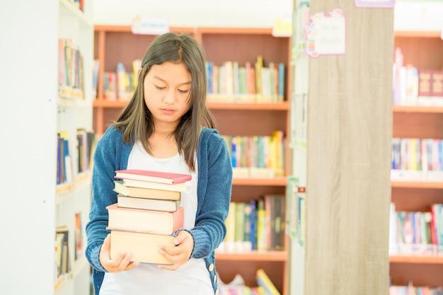 Portret van slimme student met open boek die het lezen in universiteitsbibliotheek