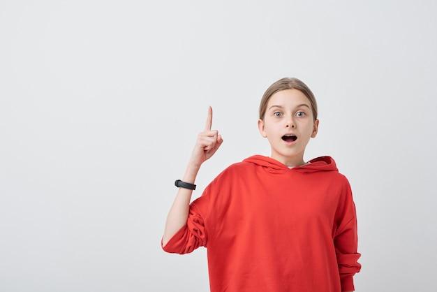Portret van slimme tiener in rode trui wijsvinger verhogen terwijl het hebben van idee