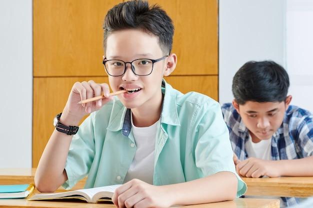 Portret van slimme vietnamese schoolstudent zittend aan een bureau met geopende boek en kauwpotlood