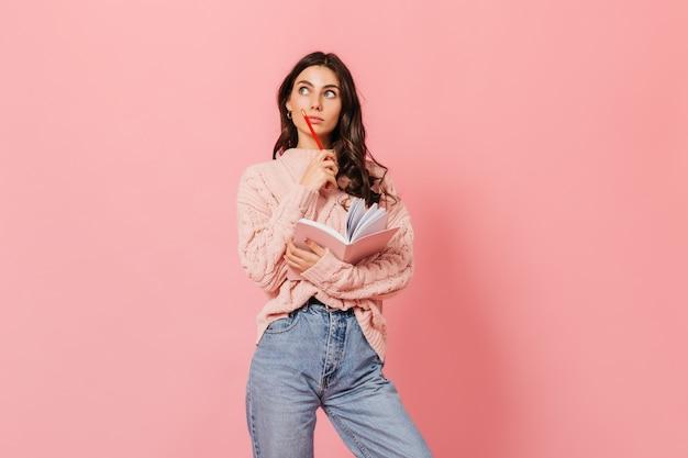 Portret van slimme vrouwelijke student met notitieboekje en rood potlood die zorgvuldig camera tegen roze achtergrond bekijken.