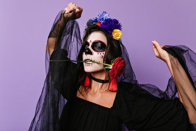 Portret van sluw en gepassioneerd meisje met ongewone gezichtskunst voor carnaval. vrouw met roos in haar mond danst op geïsoleerde muur.