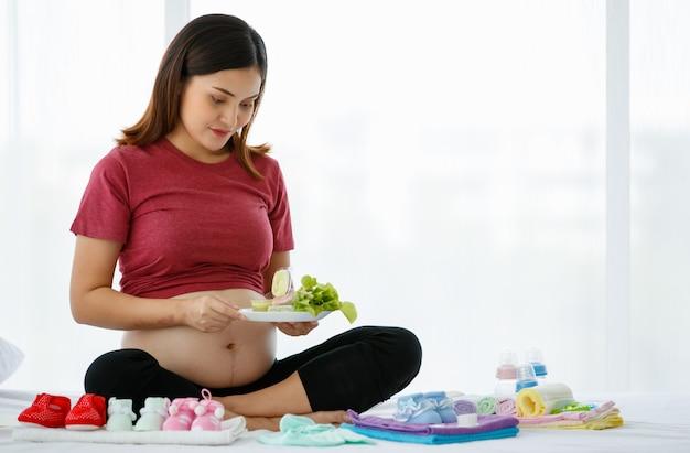 Portret van smiley actieve zwangere vrouw die zit en een bord biologische groentesalade gezond voedsel vasthoudt. ze lacht en kijkt naar een camera. gezond moederconcept.