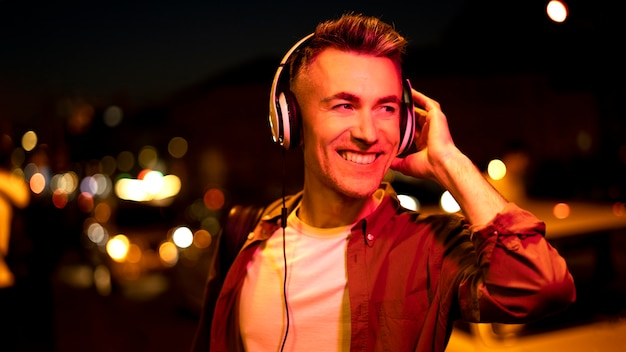 Portret van smiley man in de stad 's nachts met koptelefoon