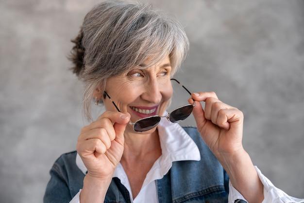 Portret van smiley senior vrouw met zonnebril