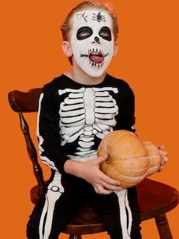 Portret van smileyjong geitje met gezicht dat voor halloween wordt geschilderd