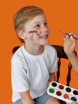 Portret van smileykind met gezicht dat voor halloween wordt geschilderd