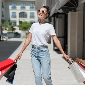 Portret van smileyvrouw die met boodschappentassen loopt