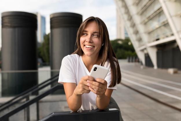 Portret van smileyvrouw stellen terwijl het houden van haar telefoon