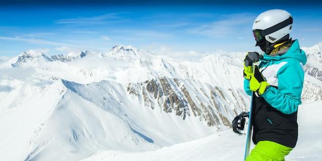 Portret van snowboarder op landschap van besneeuwde hoge bergen