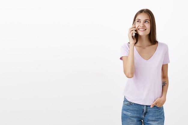Portret van sociale gelukkig en zorgeloos zelfverzekerde jonge vrouw met tatoeage in wit t-shirt glimlachend opgetogen starend terwijl smartphone in de buurt van oor praten via mobiel met vriend