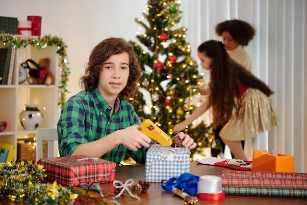 Portret van spaanse jongen dennenappels op verpakte geschenkdoos lijmen wanneer zijn zus kerstboom versieren