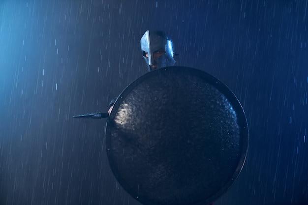 Portret van spartaanse staande buiten met speer. vooraanzicht van man in helm verstopt achter groot ijzeren schild en wijzend wapen in slecht bewolkt regenachtig weer. oud sparta-concept.