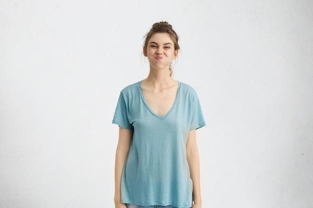 Portret van speelse grappige tiener die een blauw t-shirt draagt met plezier binnenshuis, adem inhoudt, haar best doet om niet in lachen uit te barsten terwijl vrienden haar aan het lachen proberen te maken. menselijke emoties