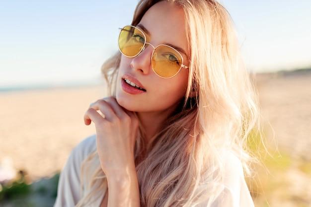 Portret van speelse lachende blonde meisje spelen met haren, plezier en genieten van de zomer op het strand close-up.