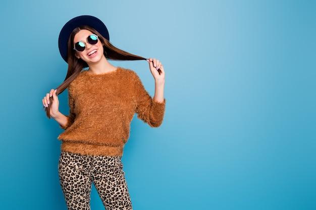 Portret van spontaan mooi schattig mooi meisje geniet van herfstvakantie touch kapsel draag goede lok kleding geïsoleerd over blauwe kleur muur
