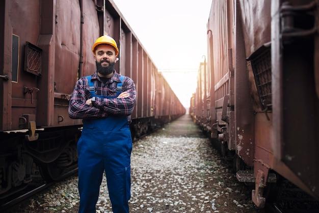 Portret van spoorwegarbeider met gekruiste armen die trots op station tussen wagons staan