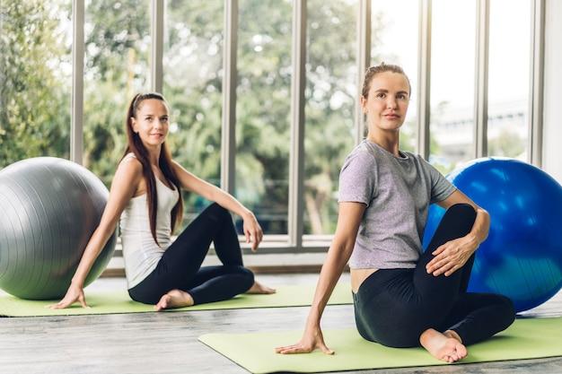 Portret van sport aantrekkelijke mensen vrouw in sportkleding zitten ontspannen en het beoefenen van yoga fitness oefening met blauwe fitball in klasse training bij sportclub