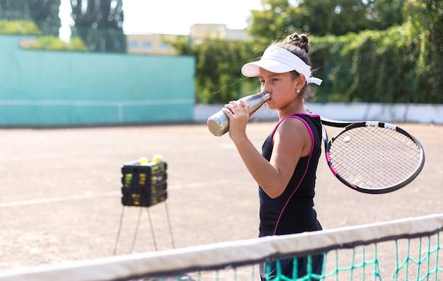 Portret van sport tienermeisje op de tennisbaan, leunen tegen het net met herbruikbare thermofles voor water en racket in de hand