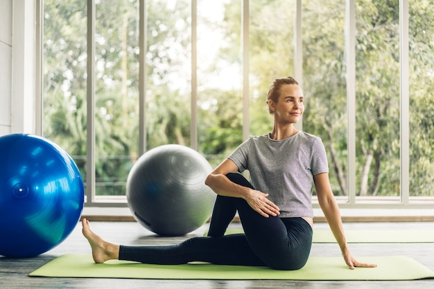 Portret van sport vrouw in sportkleding zitten ontspannen en het beoefenen van yoga fitness oefening met blauwe fitball thuis