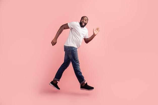 Portret van sportieve energieke man springen rennen op roze achtergrond