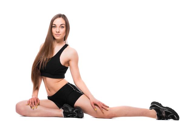 Portret van sportieve fit vrouw in sportkleding uit te werken, oefeningen te doen geïsoleerd op een witte achtergrond