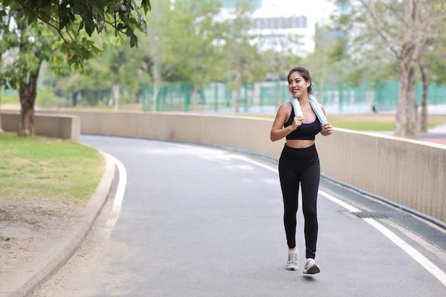 Portret van sportieve jonge aziatische vrouw in sportkleding die buiten jogt voor marathontraining. jogger meisje oefenen langs betonnen pad buiten met groene boom achtergrond. sportconcept