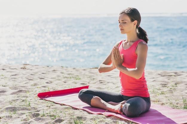 Portret van sportieve jonge vrouw doet meditatie buiten