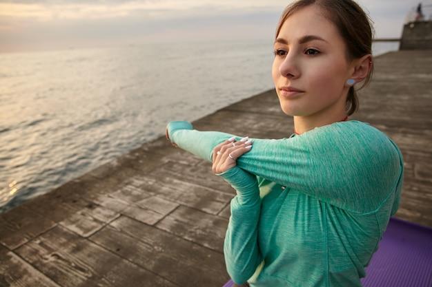 Portret van sportieve jongedame in heldere sport draagt, maakt ochtendstrekken, treinen aan zee, voelt goed en geniet van de ochtend.