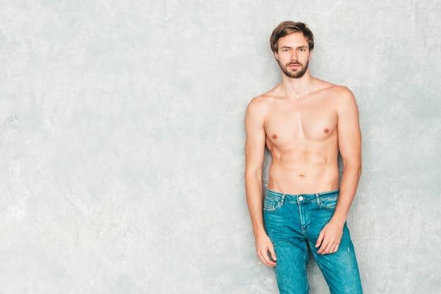 Portret van sportieve knappe sterke man. gezond lachend atletisch fitnessmodel poseren in de buurt van grijze muur in spijkerbroek.