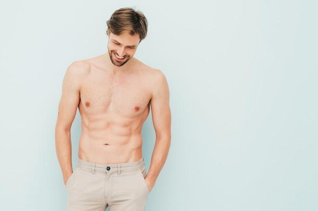 Portret van sportieve knappe sterke man. gezond lachend atletisch fitnessmodel poseren in de buurt van lichtblauwe muur