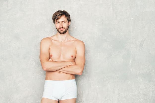 Portret van sportieve knappe sterke man. gezonde atletische fitness model poseren in de buurt van grijze muur in spijkerbroek.