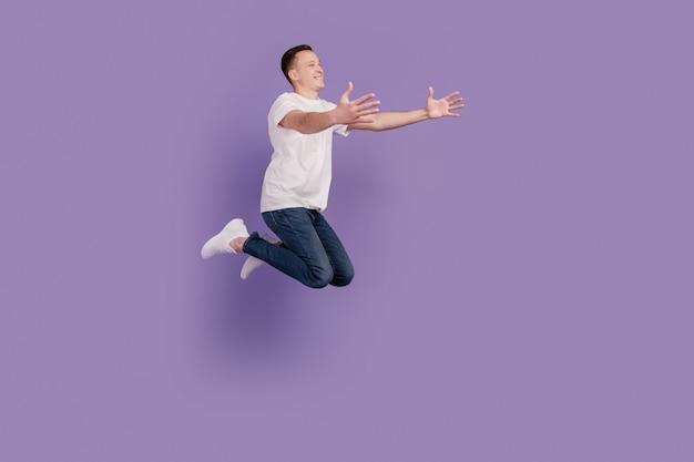 Portret van sportieve man springen handen vangen lege ruimte op violette achtergrond