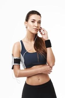 Portret van sportieve vrouw in hoofdtelefoons en sportkleding het stellen op wit.