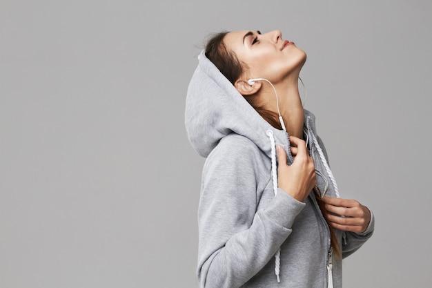 Portret van sportieve vrouw in kap en hoofdtelefoons die op wit glimlachen.