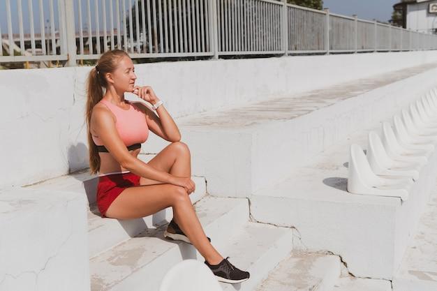 Portret van sportieve vrouw met lang haar in sportkleding in het stadion