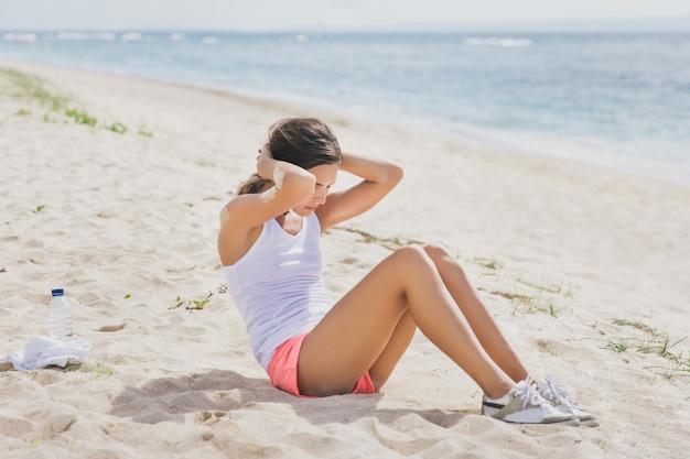 Portret van sportieve vrouw zitten op het strand