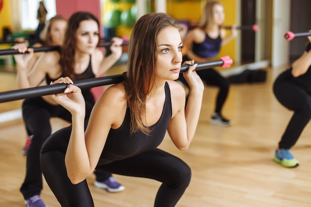 Portret van sportieve vrouwen die met barbell in geschiktheidsclub uitoefenen