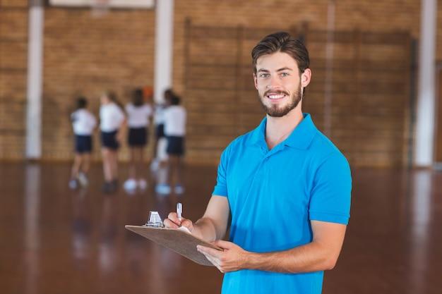 Portret van sportleraar die op klembord schrijven