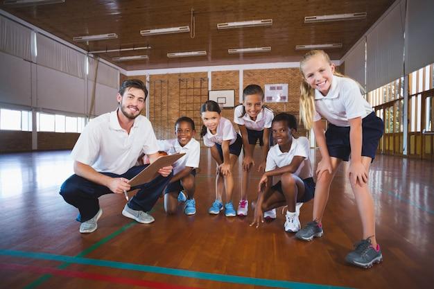 Portret van sportleraar en schoolkinderen in basketbalveld